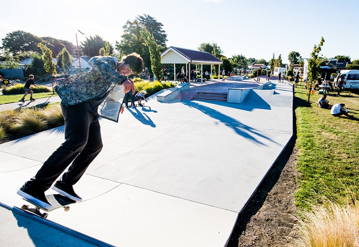 A skateboarder at the top of a shallow half-pipe in a grassed area with people in the paths and grassed area in the background