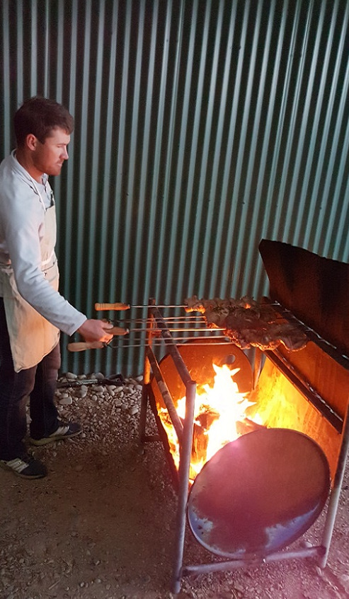 A man in white shirt and apron barbecuing meat on long skewers over a half drum barbecue