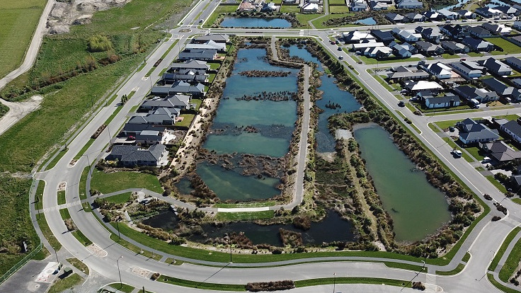 aerial image of a rectangular wetland pond surrounded by a road and houses