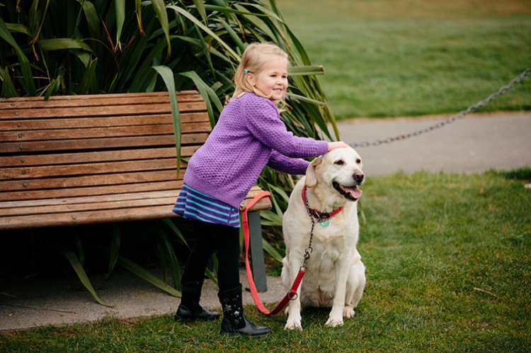 Young girl in a purple jersey and black trousers stands in a park with her hands on the head of a blonde labrador retreiver