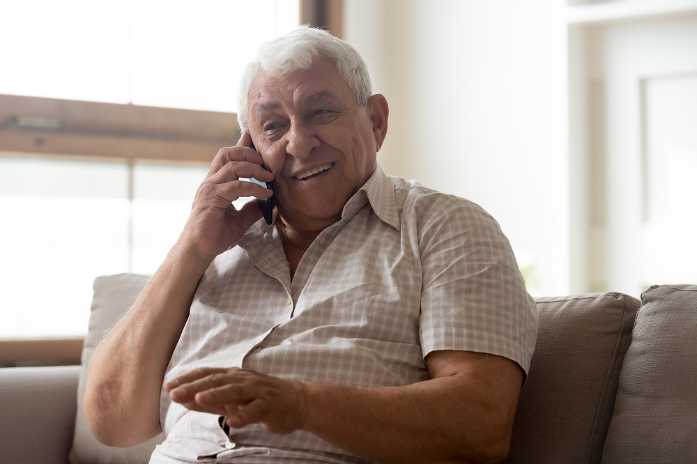 Older man talking on the phone sitting on a couch in a lounge
