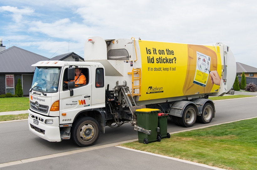 A recycling truck picking up a yellow recycling bin from the kerbside