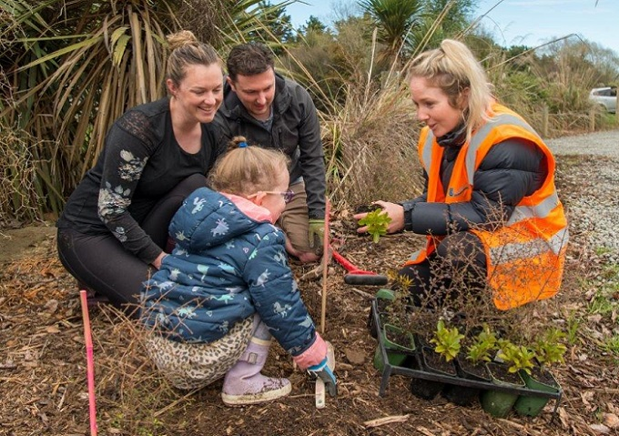 A mum, dad and young daughter talk to a woman in a high-viz jacket as they plant a tree together