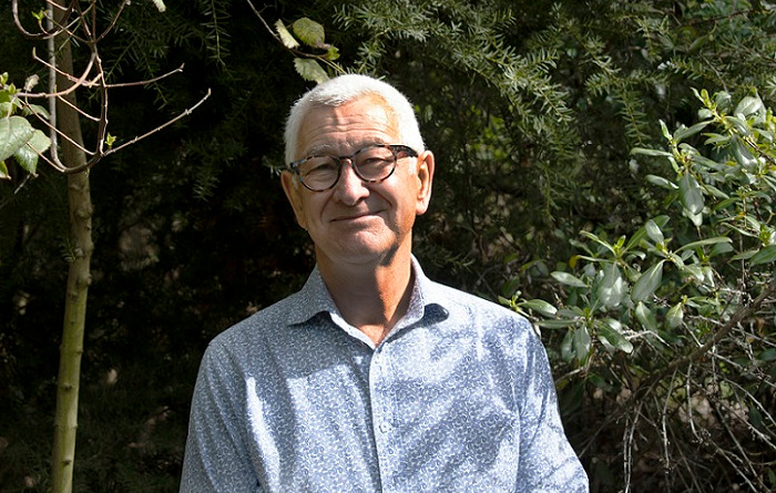 A man with short white hair and glasses stands in front of some bush