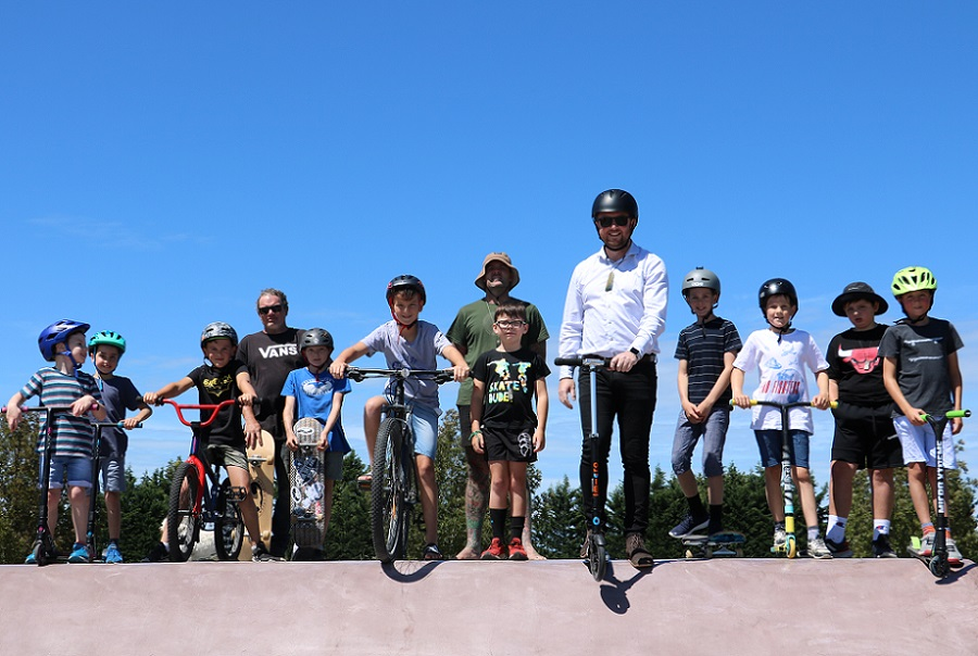 A line of of children and Mayor Sam Broughton on a range of skateboards, scooters and bikes at the top of a ramp