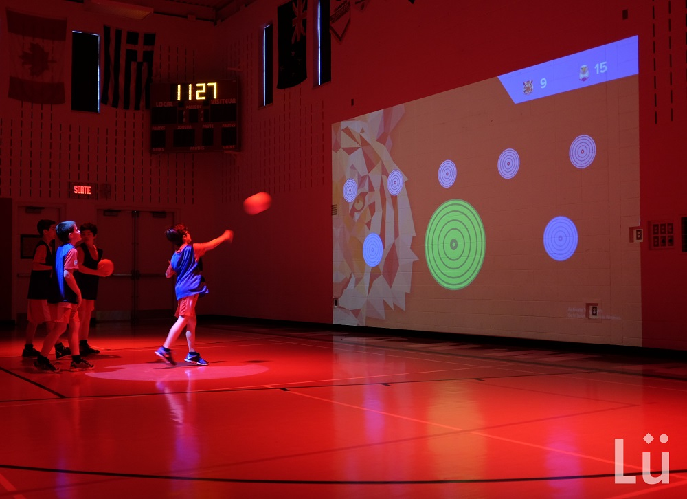Children throw a ball at a target on a wall in a gym filled with red light