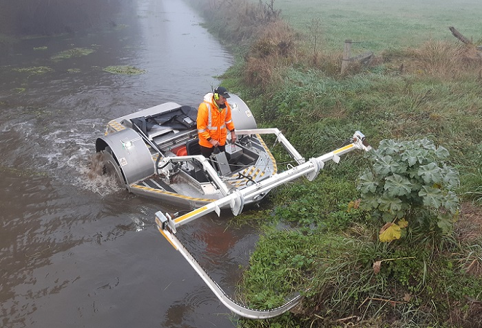 A boat in the river with its weed cutter on the front reaching up onto the bank