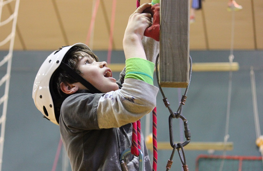 Black haired boy in white climbing helmet and grey t-shirt holding a red climbing hold and looking up for next hold