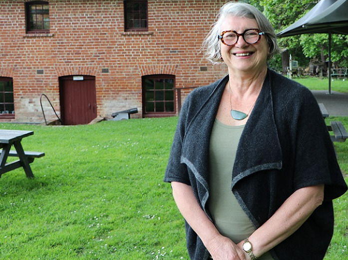 A smiling grey haired woman in round glasses, wearing a black jacket, stands on a lawn in front of a brick building