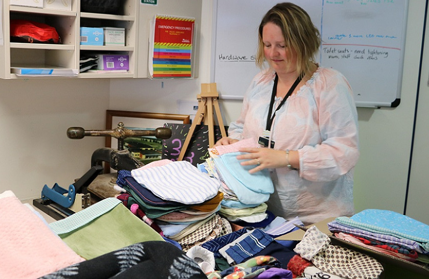 Woman lifts a pair of blue and pink sewn large pocket shaped items from the top of a table covered in similar multi coloured stacked items