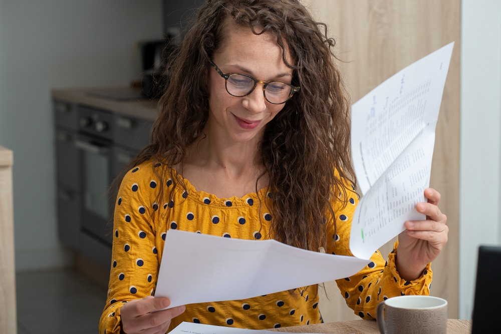 Smiling woman with long curly hair and yellow top with black spots looks through some paperwork