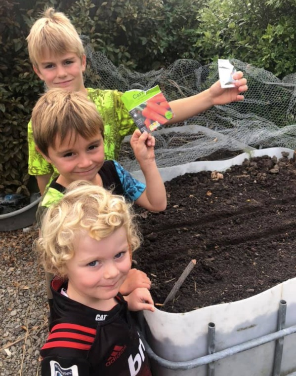 Three blonde children stand in a line holding out seed packets next to a large plastic container filled with earth