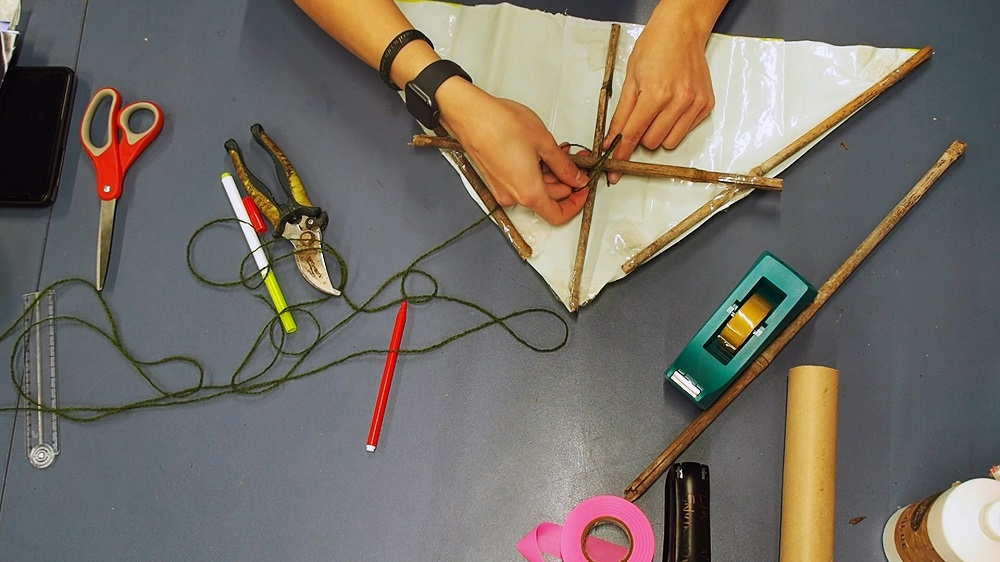 A close up of a pair of hands making a kite, surrounded by craft supplies