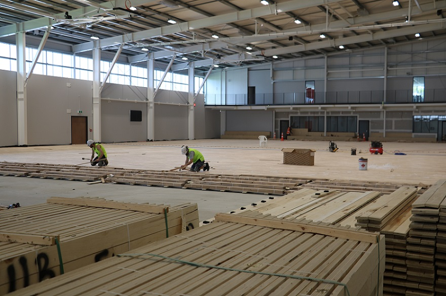 Two men nail down wooden floor boards at the Selwyn Sports Centre