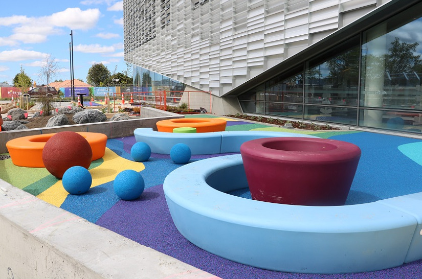 Colourful balls and curved seats on brightly coloured soft fall flooring next to Te Ara Ātea