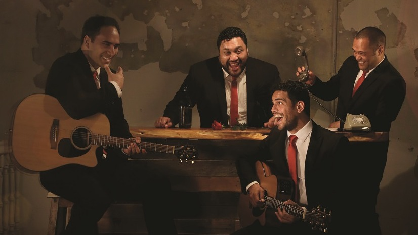 The four members of the Modern Maori Quartet laughing, two members playing guitars in front of a piano and two members behind laughing