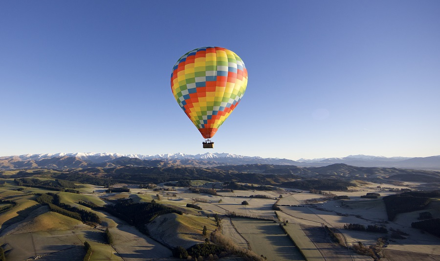 A hot air balloon in rainbow colours floating in a blue sky above the Canterbury Plains