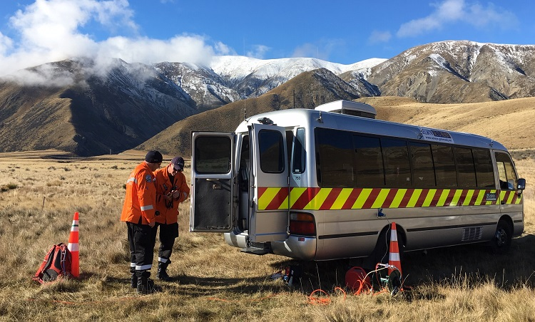 Two people in orange high visibility jackets stand behind a silver van with a red a yellow band along the side under the window line. The van is parked in a field of brown tussock at the foot of some mountains with a light dusting of snow on them