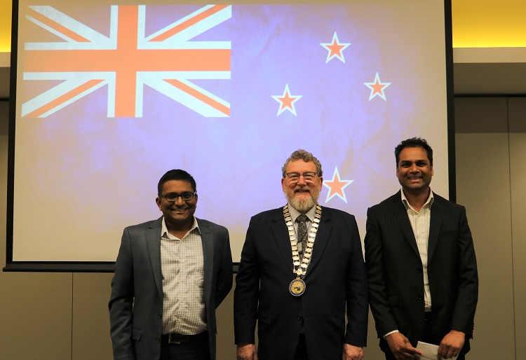 Two Indian men in suits stand either side of Deputy Mayor Malcolm Lyall with a New Zealand flag projected onto a screen behind