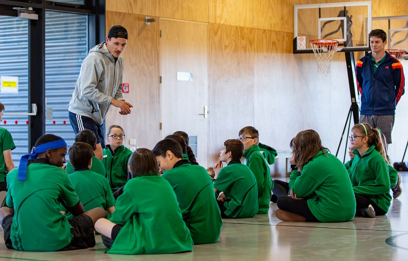 A man in a backwards black baseball cap, grey hoodie and blue sport shorts talks to a group of school children in green jerseys sitting on a gym floor, watched by a brown haired man in a blue tracksuit top with red striped sleeves