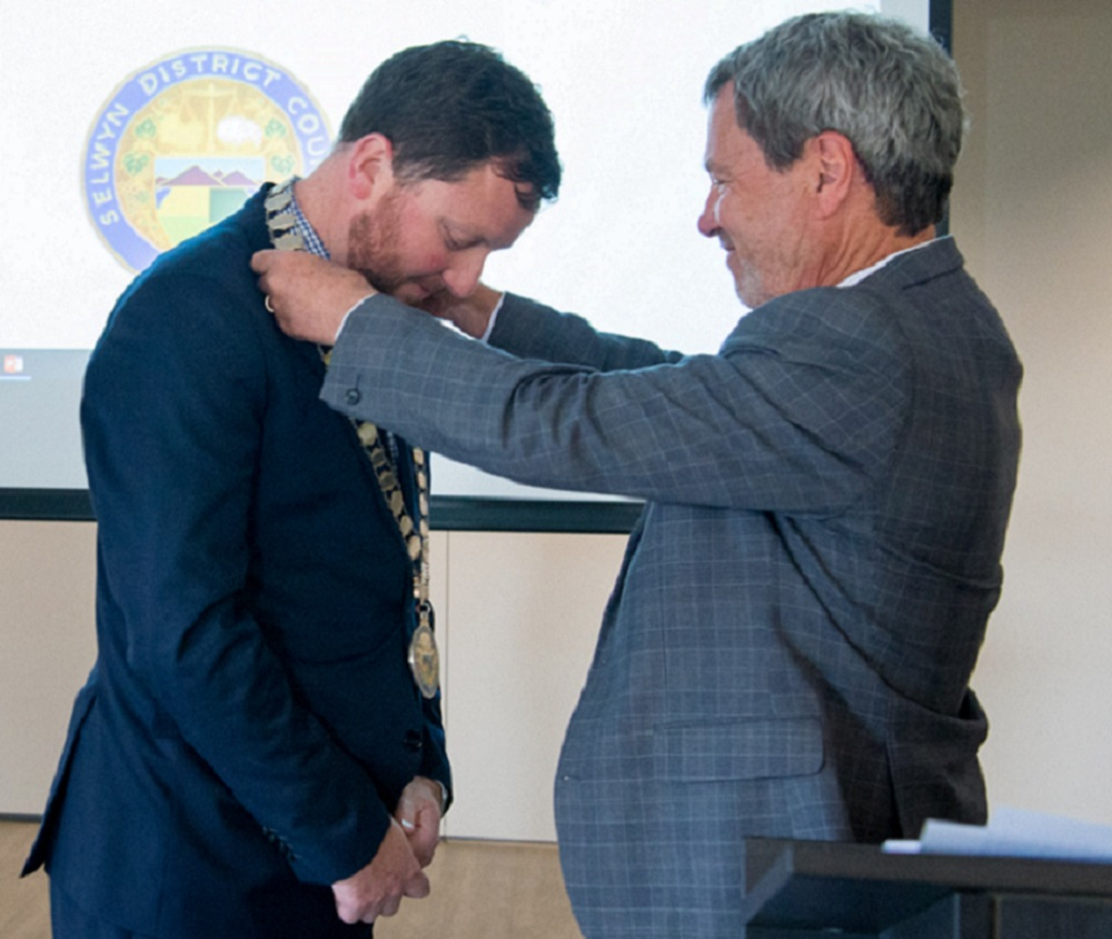 Mayor Sam Broughton, in a blue suit, with brown hair and beard, has his neck bowed as Council Chief Executive David Ward, in a grey suit, with grey hair, puts the Mayoral chains on him