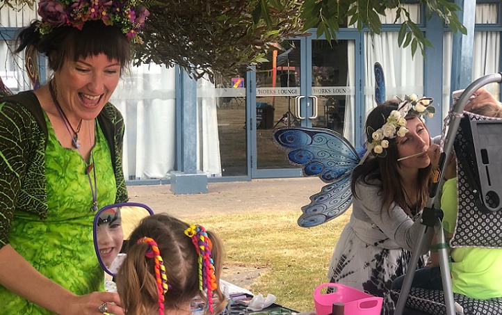 A woman dressed as a fairy in bright green smiles as she holds up a mirror to a young girl getting face painted while a woman dressed as a blue fairy paints another child's face