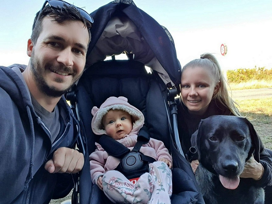 A young family, dad, baby in a pram, mum and a black labrador on a walk