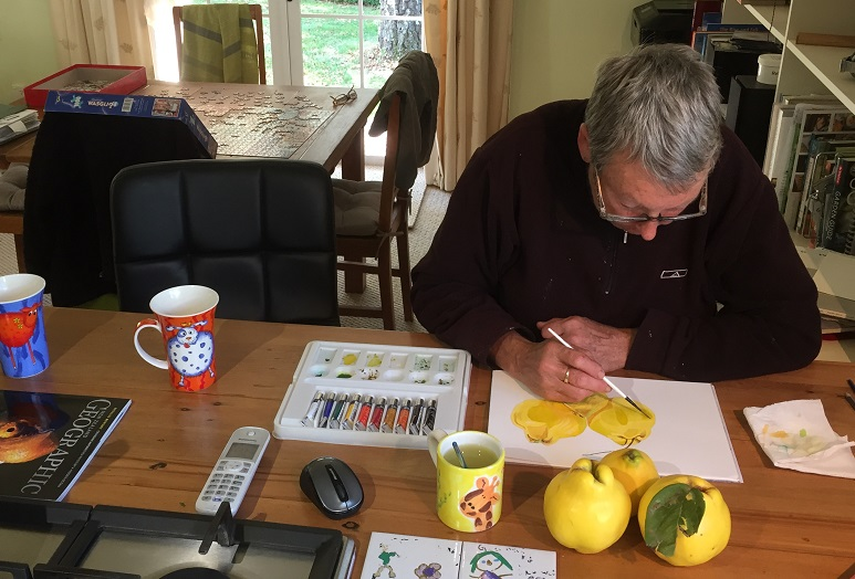 Woman with short grey hair painting quinces at a kitchen table