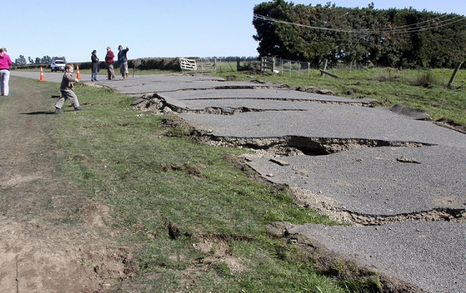 A group of adults inspect an earthquake cracked road while children play near it