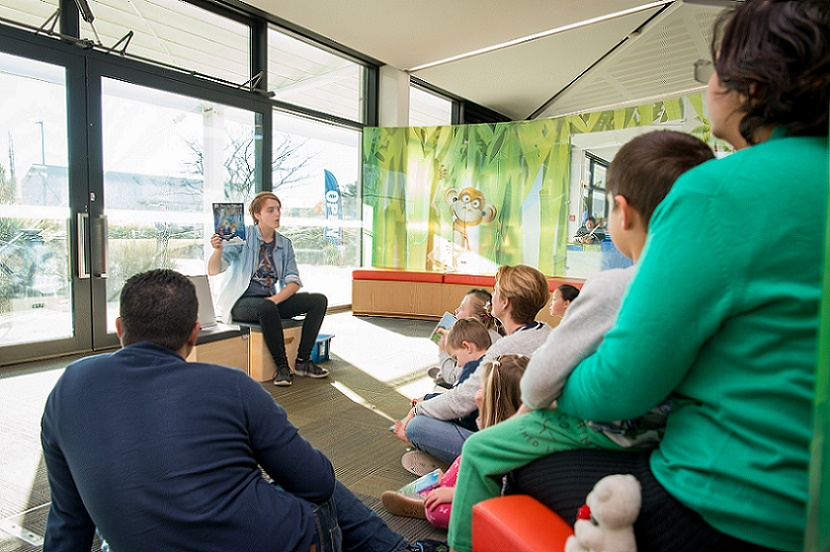 A group of families watch a reading in te reo at the library