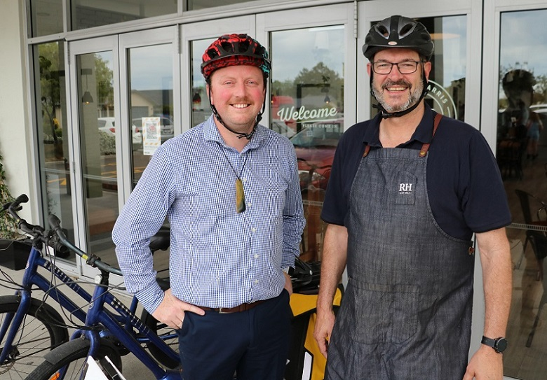 Mayor Sam Broughton and Rolleston Robert Harris Cafe owner Phil Deans with their cycle helmets on and bikes in the background