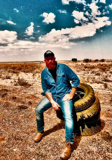 Promotional image of Adam McGrath sitting on a stack of old tires next to a barbed wire fence