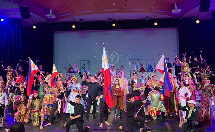 A crowd of people in traditional Filipino dress dancing with flags