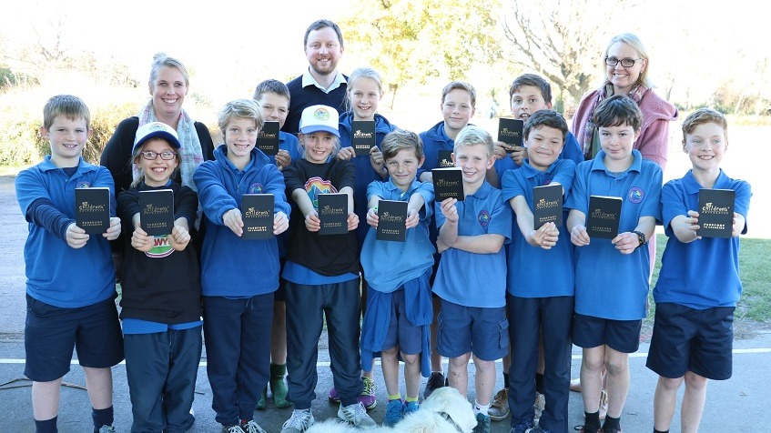 Children in two rows wearing blue school uniforms, two wearing white hats and black t-shirts with Selwyn District logo hold up small black books titled Children's University in front of two teachers and Mayor Sam Broughton