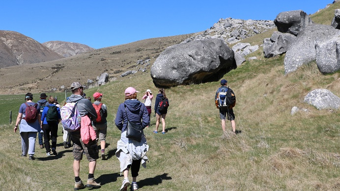 A group of walkers walk to the right of boulders at Castle Hill