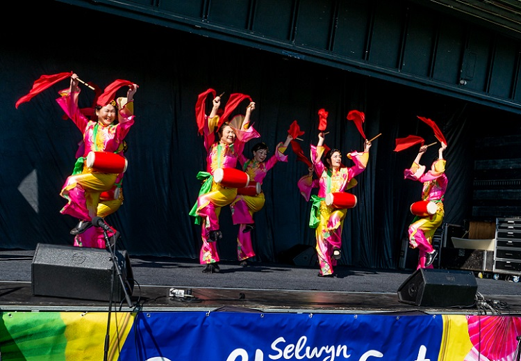 A group of women in brightly coloured pink and green traditional Chinese costumes dance and play red drums, waving drum sticks with red scarves attached