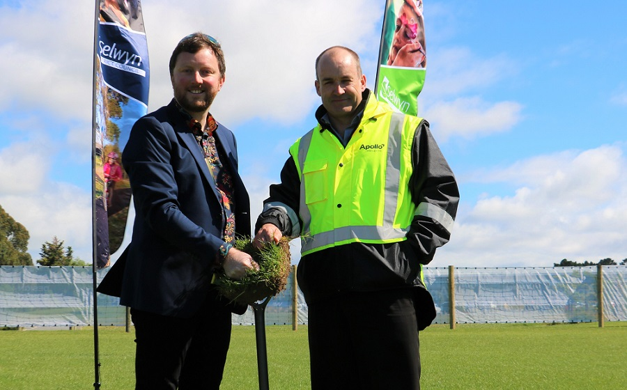 Mayor Sam Broughton and Appollo Projects CEO Paul Lloyd wearing an Apollo branded high visibility vest hold up a sod of earth