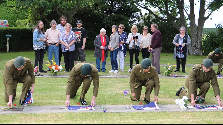 Four soldiers in dress uniforms kneel and lift flags from plaques while family members look at plaques on a row behind