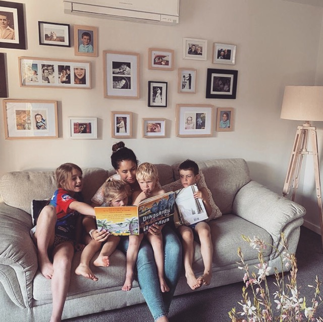 A mum and four young children sit on a couch reading a story and pointing at the pictures