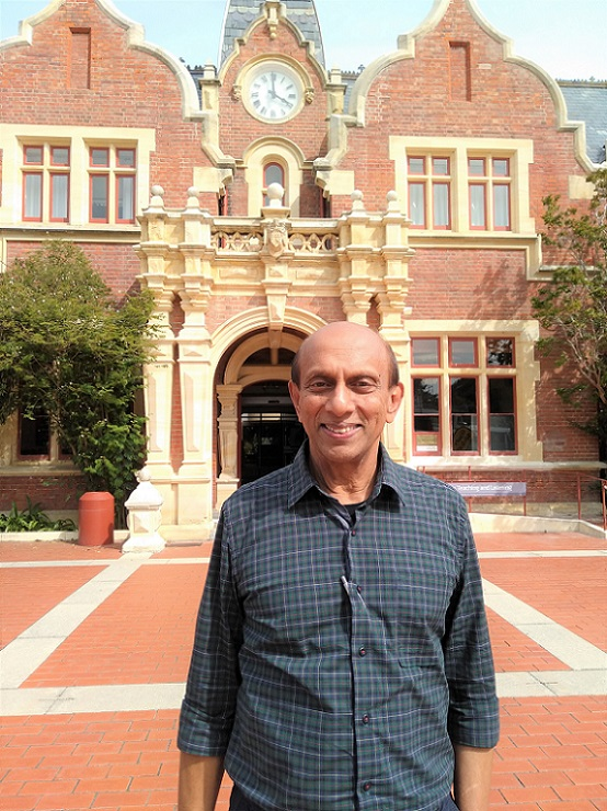 A smiling Sri Lankan man stands in front of a heritage brick building at Lincoln University
