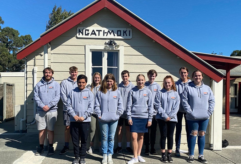 The Youth Council in grey hoodies standing in front of a building at Ngati Moki marae