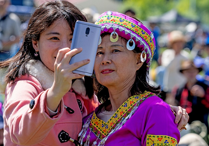 Two women, one in traditional Chinese dress, share a selfie