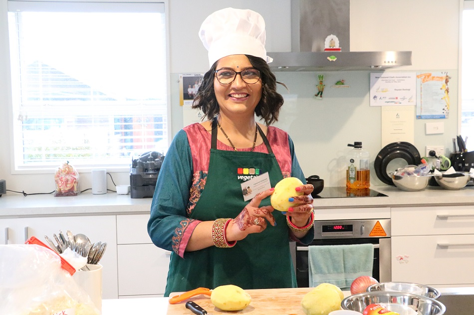 A woman in a home kitchen wearing a chef's hat and pealing a potato