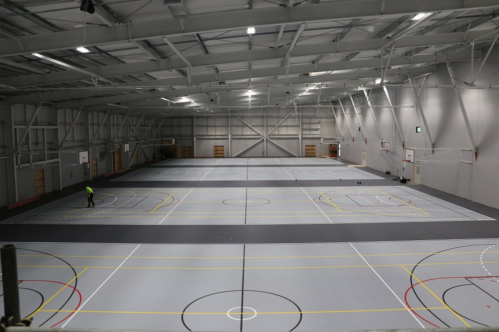 A view from above of the courts at the Selwyn Sports Centre with a man painting lines on a court