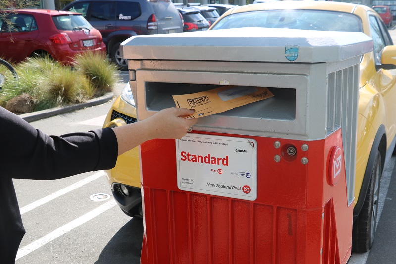 A person puts an orange voting envelope into a post box