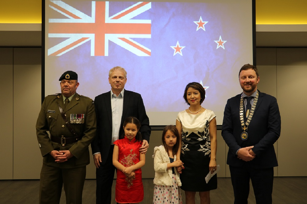 A New Zealand Army officer in full uniform stands next to a tall man with white blonde hair with his arm on the shoulder of a young girl in a red dress, a young girl in a white dress holds the arm of a Chinese woman in a black and white dress standing next to Mayor Sam Broughton wearing his Mayoral chains