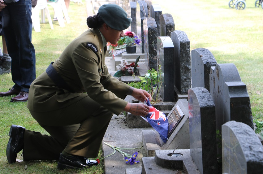 A female soldier in a dress uniform kneels and removes the flag from a plaque