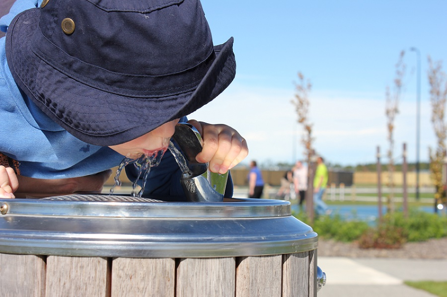 A boy in a blue sun hat drinks from a drinking fountain