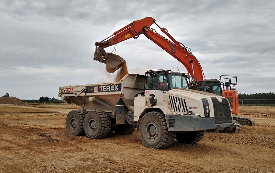 A digger drops a scoop of dirt into the back of a dump track. Both are on a patch of bare brown earth