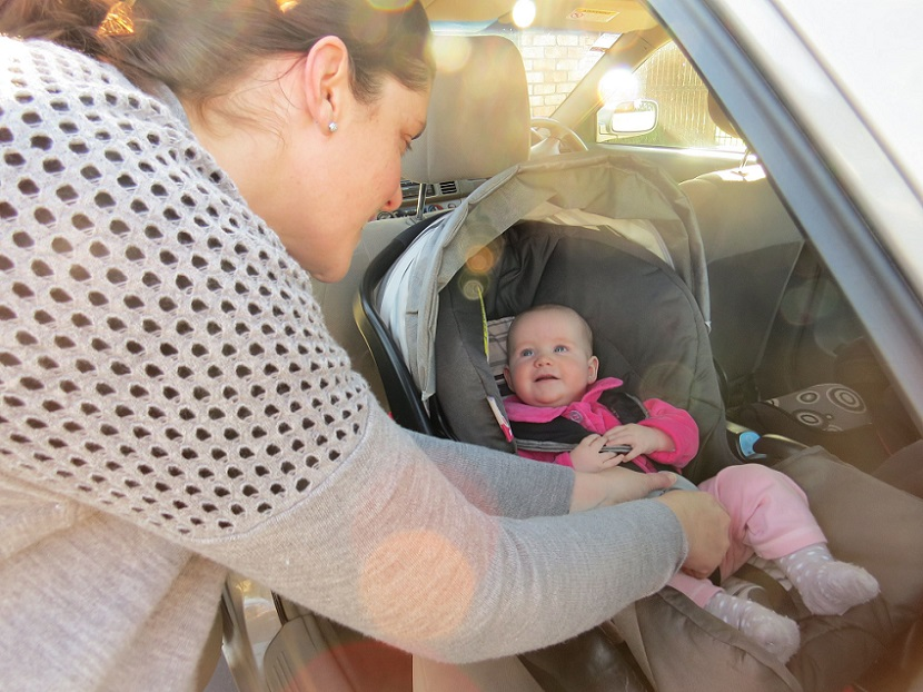 Mum clipping baby into car seat